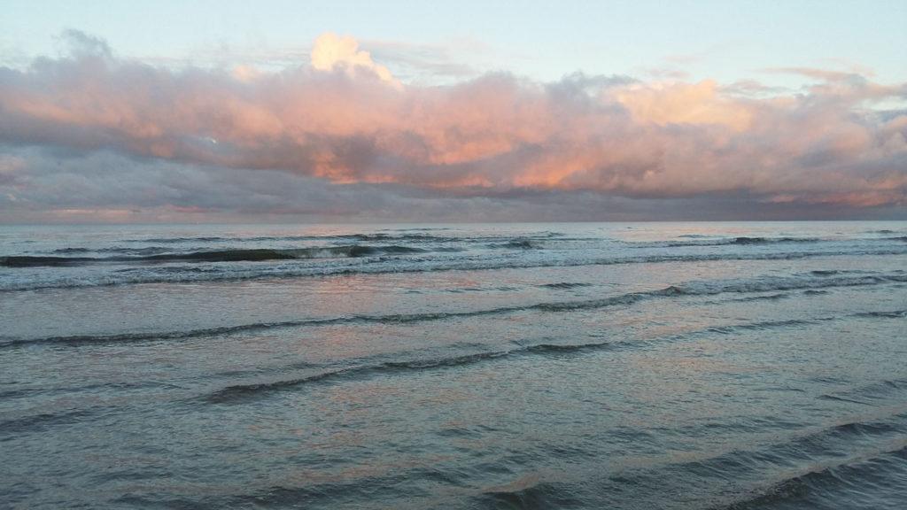 Rosa Wolken leuchten über blauen Wellen