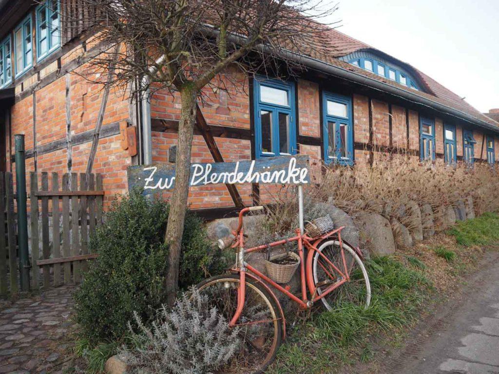 """Rotes Fahrrad vor Backsteinhaus mit blauen Fenster und Schild """"Zur Pferdetränke"""""""