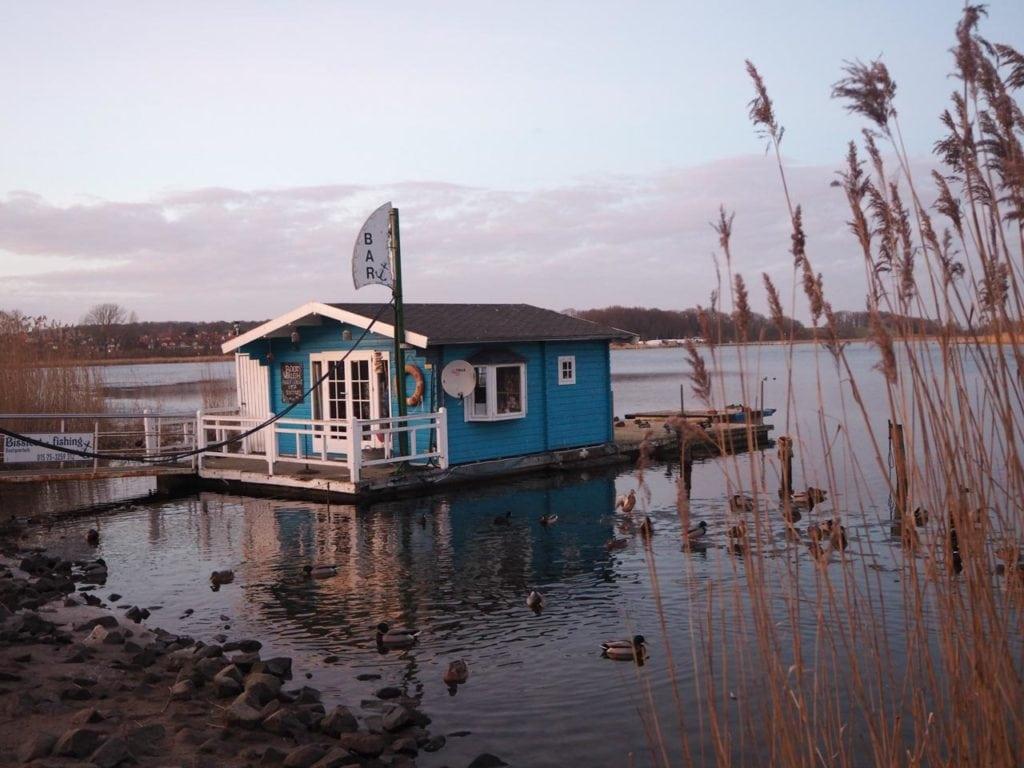 Kleines blaues Hausboot, auf dem umgebenden Wasser schwimmen über zehn Enten