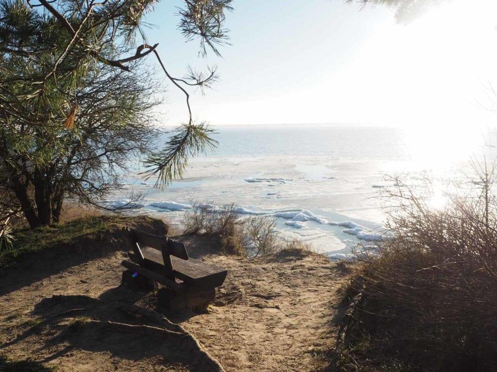 Bank am Rande der Steilküste mit Blick auf das zugefrorene Wasser