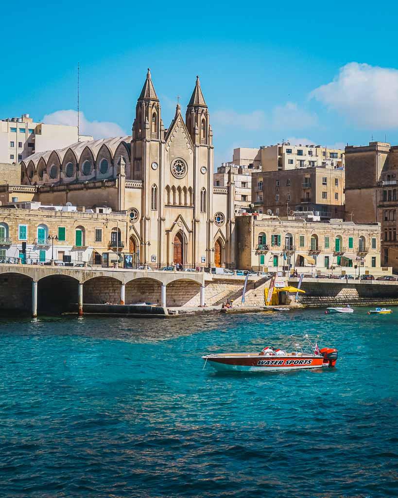 Motorboot auf türkisblauem Wasser in der Balluta Bay