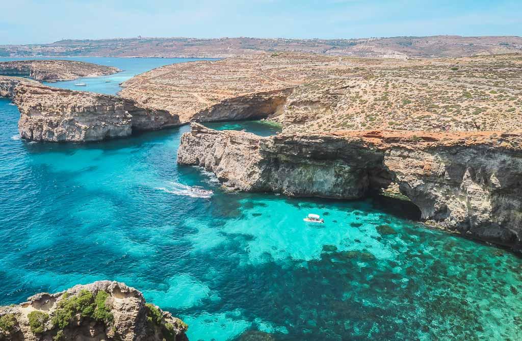 Zwei Boote in der Chrystal Lagoon und der Blick auf die trockene Landschaft Maltas
