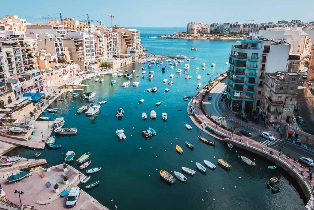 Blick auf einen Bucht zwischen hohen Häusern mit vielen kleinen, weißen Booten