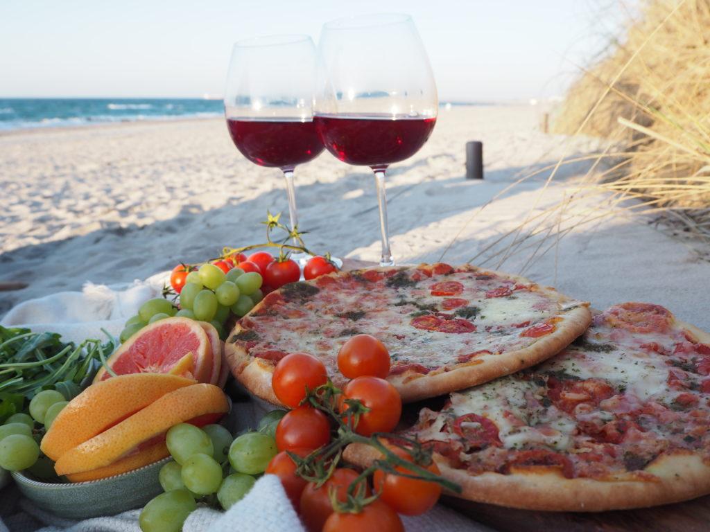 Picknick am Ostseestrand mit Pizza und Rotwein